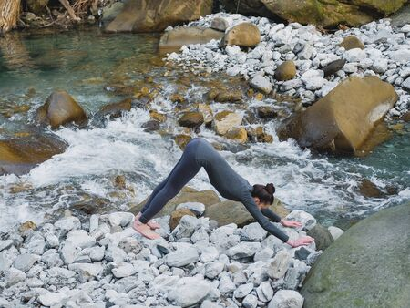Young slim woman practicing yoga outdoors on stone shore of mountain river. Unity with nature concept. Girl in dog pose downward facing.