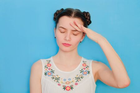 Funny cute girl on a blue studio background. Bright emotional female portrait. Headache drama face. 스톡 콘텐츠