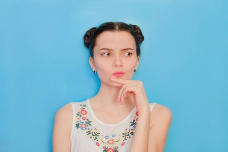 Funny cute girl on a blue studio background. Bright emotional female portrait. Thoughtful face looking away.