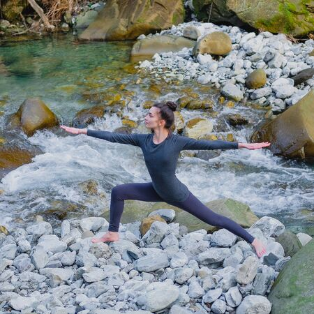 Young slim woman practicing yoga outdoors on stone shore of mountain river. Unity with nature concept. Girl standing in warrior pose. 스톡 콘텐츠