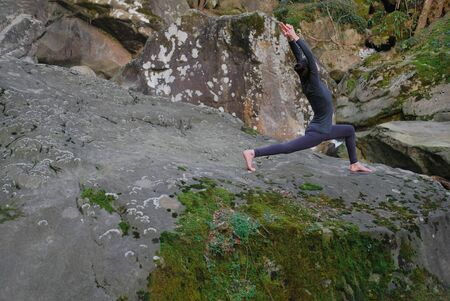 Young slim woman practicing yoga outdoors on big moss rock. Unity with nature concept. Girl doing Crescent lunge.