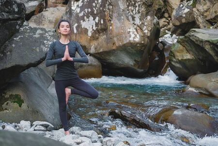 Young slim woman practicing yoga outdoors on stone shore of mountain river. Unity with nature concept. Girl standing in tree pose