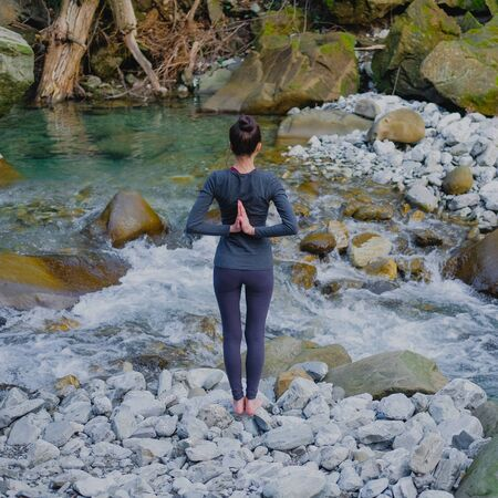 Young slim woman practicing yoga outdoors on stone shore of mountain river. Unity with nature concept. Girl standing back with reverse prayer hands.