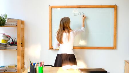 Female teacher writing on the marker board im classroom. Education concept english language lesson.