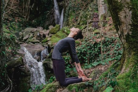 Young slim woman practicing yoga outdoors in moss forest on background of waterfall. Unity with nature concept. Girl in camel position.