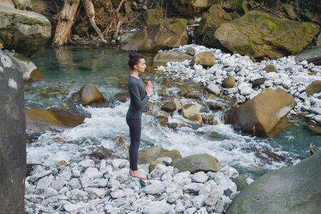 Young slim woman practicing yoga outdoors on stone shore of mountain river. Unity with nature concept. Girl standing in profile with prayer hands.