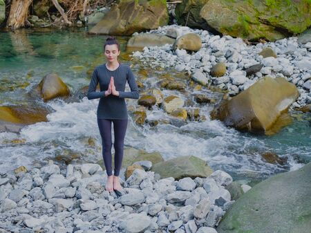 Young slim woman practicing yoga outdoors on stone shore of mountain river. Unity with nature concept. Girl standing with prayer hands.