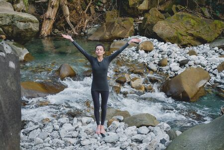 Young slim woman practicing yoga outdoors on stone shore of mountain river. Unity with nature freedom concept. Girl standing rising arms up.