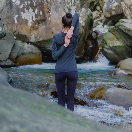 Young slim woman practicing yoga outdoors on stone shore of mountain river. Unity with nature concept. Girl doing back hands lock. Zdjęcie Seryjne