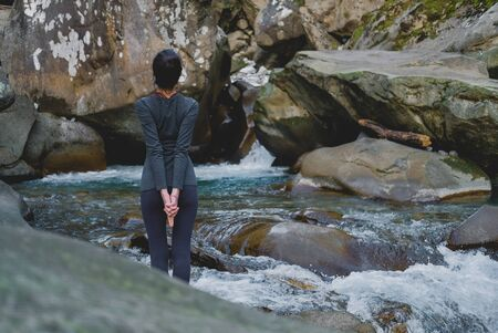 Young slim woman practicing yoga outdoors on stone shore of mountain river. Unity with nature concept. Girl standing back and stretching arms down.
