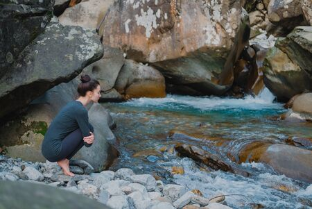 Young slim woman practicing yoga outdoors on stone shore of mountain river. Unity with nature concept. Girl sitting on tiptoes. Stock Photo