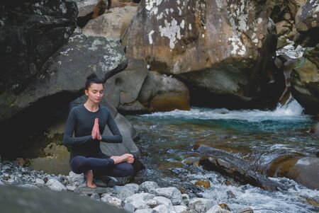 Young slim woman practicing yoga outdoors on stone shore of mountain river. Unity with nature concept. Girl sitting on tiptoes. Zdjęcie Seryjne