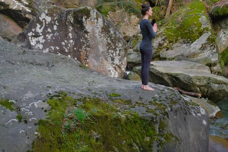 Young slim woman practicing yoga outdoors on big moss rock. Unity with nature concept. Girl standing with prayer hands. 写真素材
