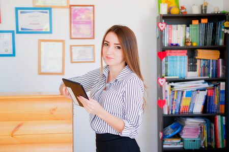 Female secretary holding tablet on background of diplomas on wall in office.