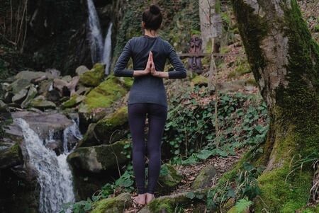 Young slim woman practicing yoga outdoors in moss forest on background of waterfall. Unity with nature concept. Girl standing with prayer hands. Zdjęcie Seryjne