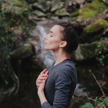 Young woman practicing breathing yoga pranayama outdoors in moss forest on background of waterfall. Unity with nature concept 版權商用圖片