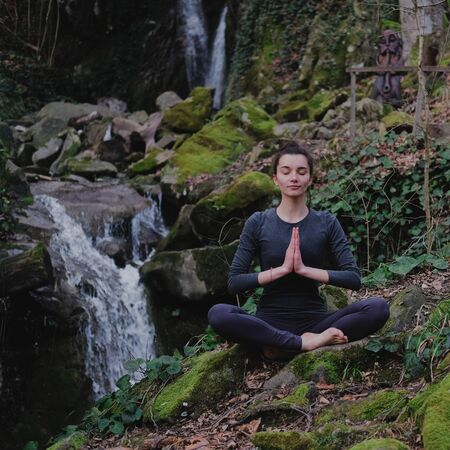 Young slim woman practicing yoga outdoors in moss forest on background of waterfall. Unity with nature concept. Girl meditates sitting.