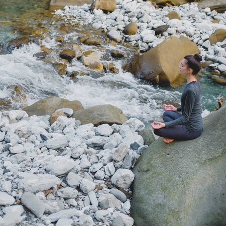 Young slim woman practicing yoga outdoors on stone shore of mountain river. Unity with nature concept. Meditation in easy pose