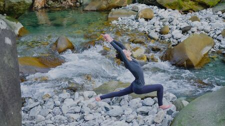 Young slim woman practicing yoga outdoors on stone shore of mountain river. Unity with nature concept. Girl doing Crescent lunge. Zdjęcie Seryjne