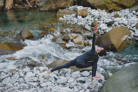 Young slim woman practicing yoga outdoors on stone shore of mountain river. Unity with nature concept. Girl standing in lunge triangle pose