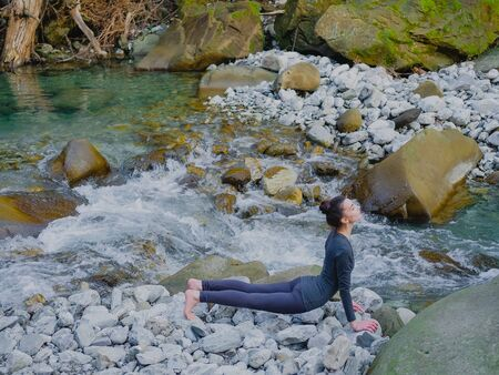 Young slim woman practicing yoga outdoors on stone shore of mountain river. Unity with nature concept. Girl doing cobra pose. 스톡 콘텐츠