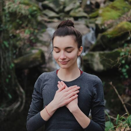Young woman practicing breathing yoga pranayama outdoors in moss forest on background of waterfall. Unity with nature concept 스톡 콘텐츠