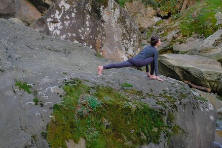 Young slim woman practicing yoga outdoors on big moss rock. Unity with nature concept. Girl doing lunge stretching 스톡 콘텐츠