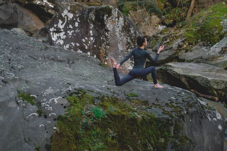 Young slim woman practicing yoga outdoors on big moss rock. Unity with nature concept. Girl stretching ham. 스톡 콘텐츠