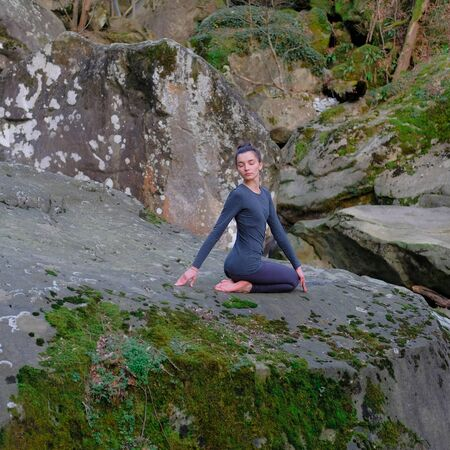 Young slim woman practicing yoga outdoors on big moss rock. Unity with nature concept. Girl in seated spinal twist pose. 스톡 콘텐츠