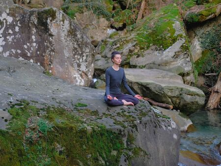 Young slim woman practicing yoga outdoors on big moss rock. Unity with nature concept. Girl meditates in easy pose.