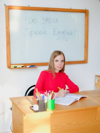Female teacher writing into class register on background of marker board in classroom. Education concept english language lesson. 스톡 콘텐츠