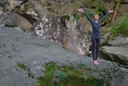 Young slim woman practicing yoga outdoors on big moss rock. Unity with nature concept. Girl standing with arms up.