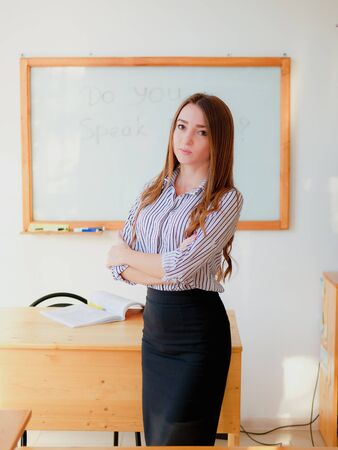 Female teacher standing at the marker board im classroom. Education concept