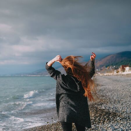 Girl in grey cardigan walking alone on empty pebble seashore in cloudy cold weather. Lonely woman freedom concept. Wind in hair.
