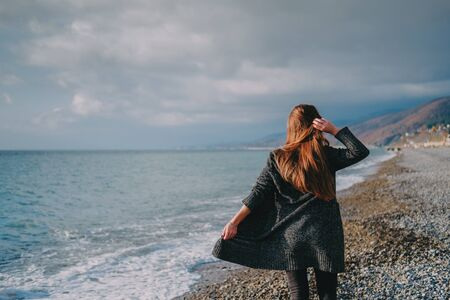 Girl in grey cardigan walking alone on empty pebble seashore in cloudy cold weather. Lonely woman freedom concept. 版權商用圖片 - 136117422