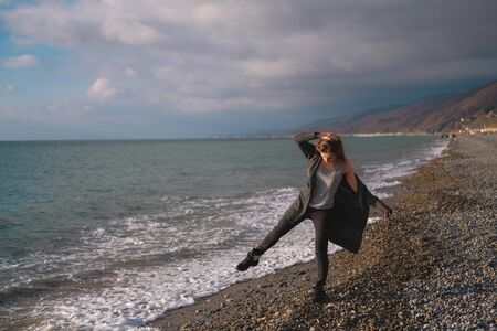 Girl in grey cardigan walking alone on empty pebble seashore in cloudy cold weather. Lonely woman freedom concept.