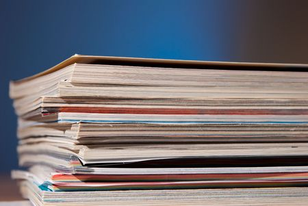 magazines on a desk isolated over a blue background Stock Photo - 6174271