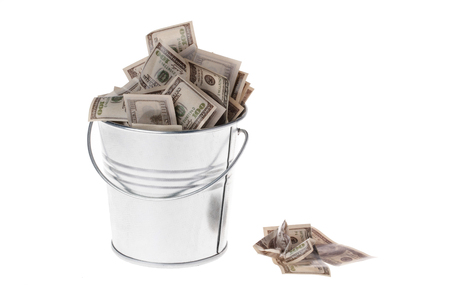 bucket of money: dollars in a metal bucket on a white background