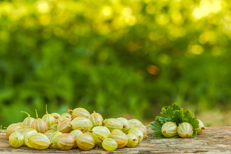 a scattering of gooseberry on a wooden table Фото со стока