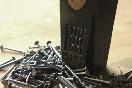 hammer head: Hammer head with the couple of nails on wooden board Stock Photo