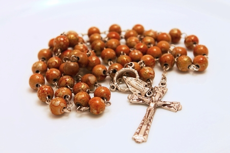 Rosary with crucifix on the white board