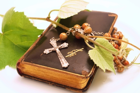 Crucifix and Old worn Prayer book on the white board  photo