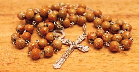 Rosary with crucifix on the wooden board  photo