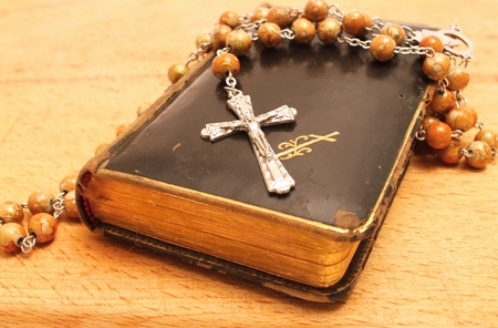 Crucifix and Old worn Prayer book on the wooden board  photo