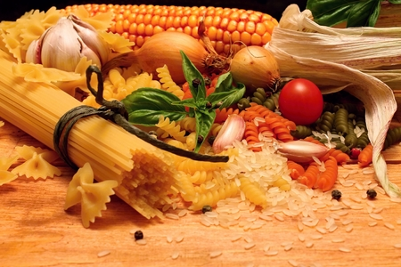 Wooden table with different kinds of pasta and vegetable photo