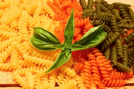 Wooden table with different kinds of colored pasta and vegetable photo