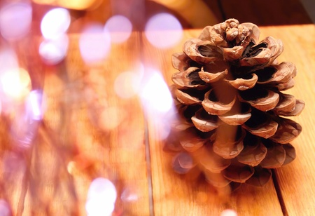 Big pinecone on wooden table with autumn decoration around and reflection marks photo