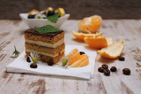 Chocolate dessert on white tissue among fruit red wine grapes, mandarine and slices of banana placed on old wooden board with bowl in background photo