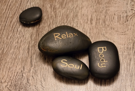 Three black lava stones with highlights on wooden board and one black blank stone near the rest Stock Photo