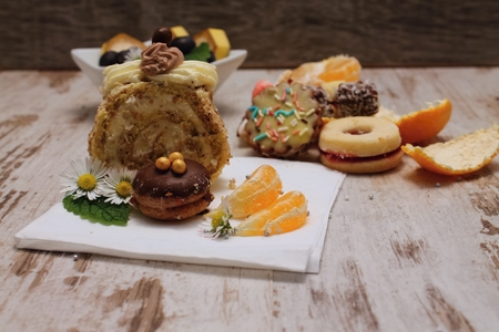 Portion of sweet coffee roulade with other sweets on wooden board with pieces of mandarin and orange bark with mint melissa leaf and daisy blooms with bowl with fruit in background photo